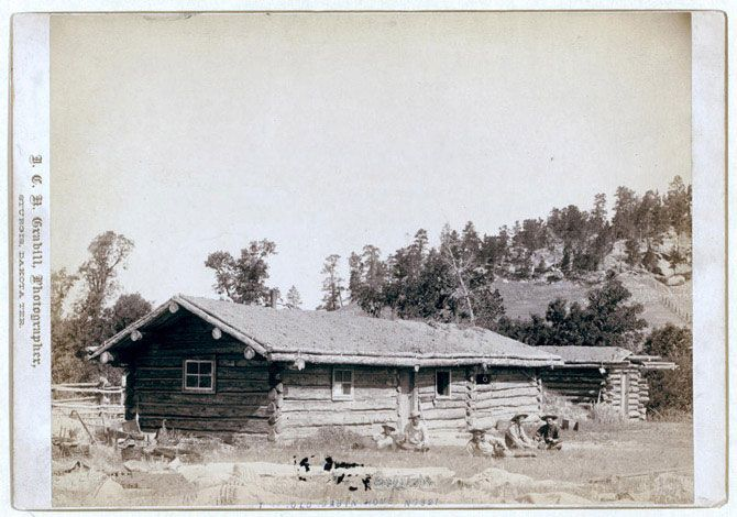 Стара хатина. П'ятеро чоловіків сидять на траві перед бревенчатой хатиною. Знімок зроблений між 1887 і 1892 роком.