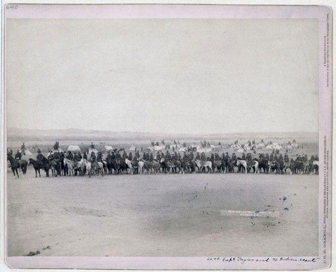 Капітан Тейлор і 70 індіанських розвідників. Довгий ряд військових і розвідників з племені лакота перед табором. Знімок зроблений в 1891 році, ймовірно на території резервації Пайн-Рідж або поруч з нею.