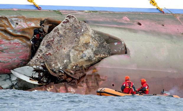 Пожежні оглядають величезні брили, що стирчать з корпусу круїзного лайнера «Costa Concordia» на наступний день після катастрофи. (AP Photo / Andrea Sinibaldi, Lapresse)