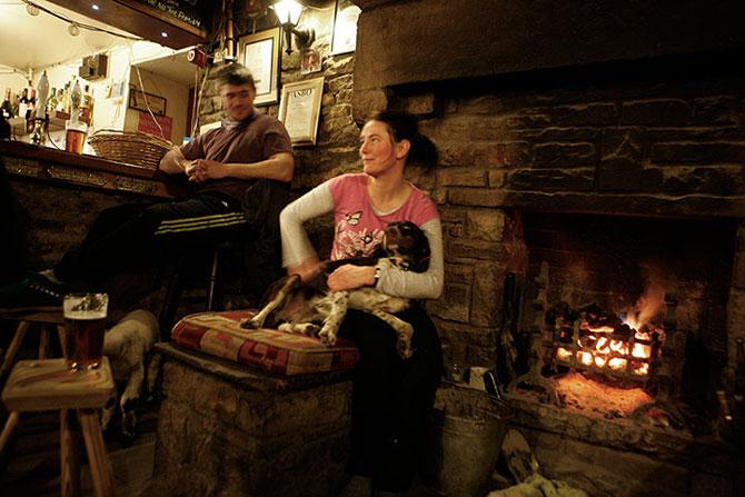 Відвідувачі гріються біля каміна в The Tan Hill Inn пабі.