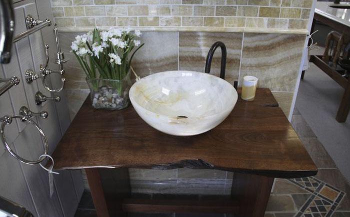 Мармурова раковина з бронзовим змішувачем на дерев'яній стільниці