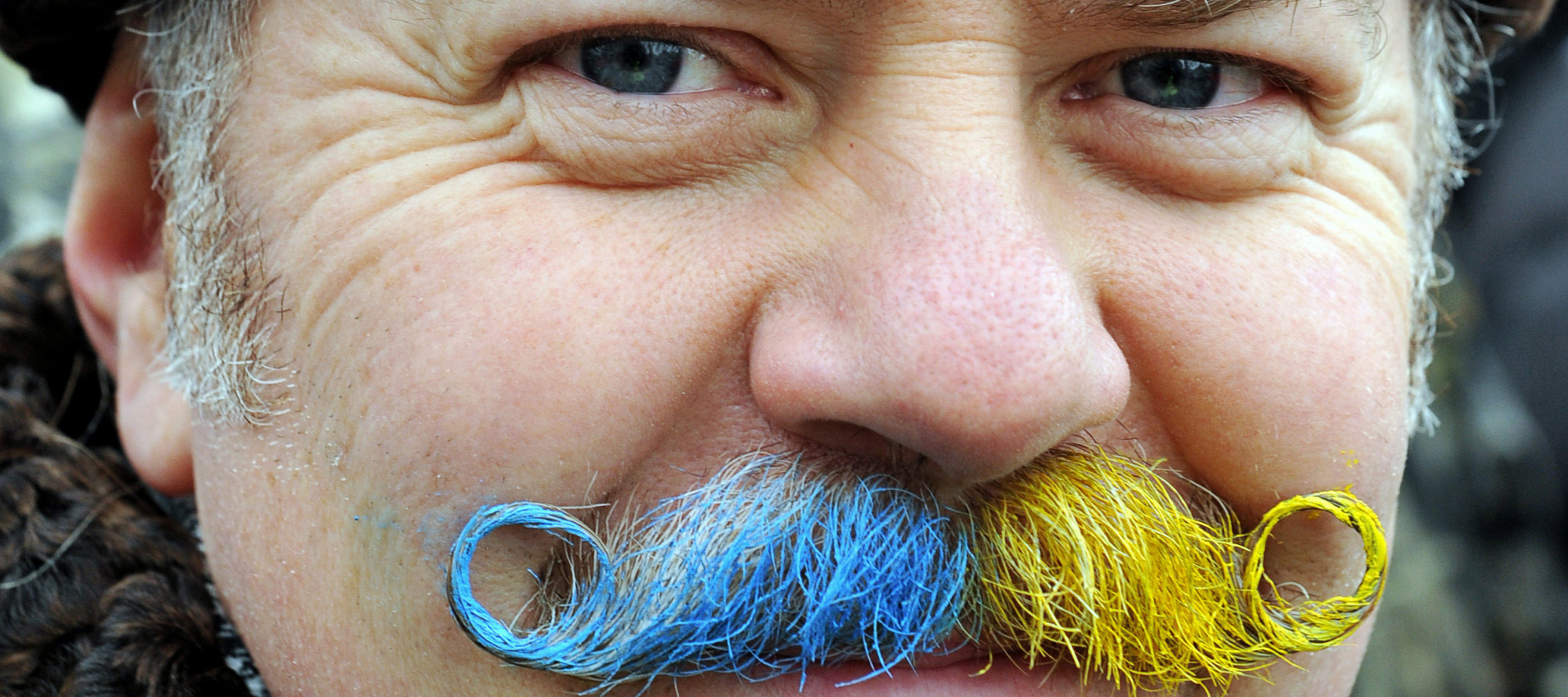 A man with a mustache painted in the colors of the Ukrainian flag poses for a photograph in Independence Square in Kiev during a mass opposition rally on December 15, 2013. At least 200,000 pro-European demonstrators began a mass rally in the Ukrainian capital today in a fresh show of force against President Viktor Yanukovych after his failure to sign a key EU agreement.  AFP PHOTO / YURIY DYACHYSHYN