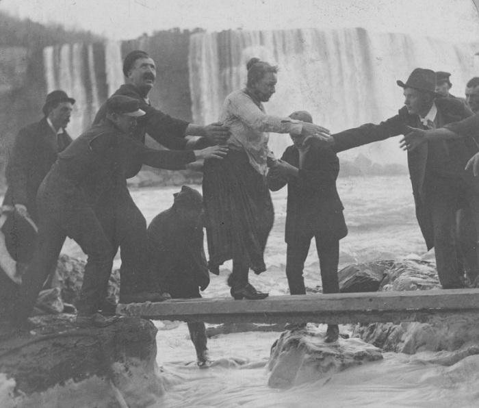 Чоловіки, які допомагають Енні Едсон Тейлор вибратися після падіння з Ніагарського водоспаду. | Фото: mashable.com.